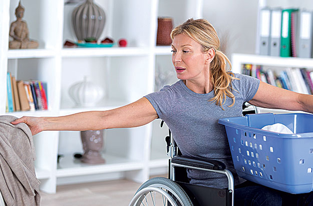 Women in wheelchair doing laundry