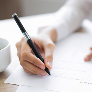 Person's hand using a pen to fill out application